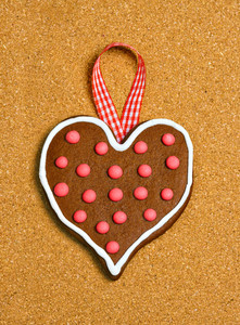 Heart shaped cookie with ribbon on cork surface