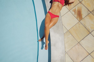 High angle view of an attractive woman lying at the edge of a pool in a bikini with her legs crossed. Female model sunbathing at poolside