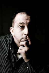 High contrast portrait of a middle aged man with a contemplative look on his face.  He could be worried or anxious about something on his mind.
