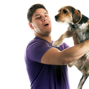 High key portrait of a young man holding a cute mixed breed dog isolated over white.