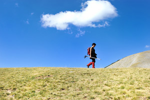 Hiker in mountains at grassland with sky above