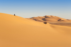 Hiker sitting atop a sand dune in the desert