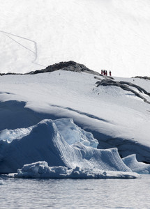 Hikers atop a snowy, rocky coast