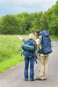 Hiking young couple backpack tramping on asphalt road countryside