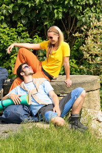 Hiking young couple watching each other relax outside summer day