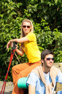 Hiking young couple with poles relax outside summer day