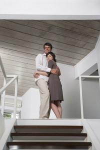 Hispanic couple embracing at home