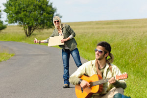 Hitch-hike young couple backpack tramping on asphalt road play guitar