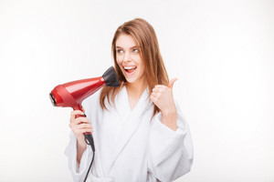 holding hair dryer and showing thumbs up