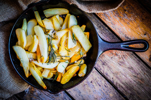 Homemade French Fries With Rosemary And Salt In Cast Iron Skillet On Wooden Rustic Background