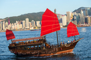 Hong Kong victoria habour with red ship and building in background.