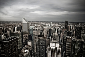 Horizontal aerial view of the Manhattan section of New York City including all of the buildings and skyline in sepia tone with vignetting.