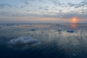 Ice floe and a cloudy sky reflected at sunset