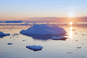 Iceberg and ice floe at sunset
