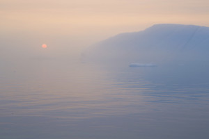 Iceberg and ice floe during a foggy sunset