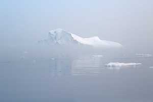 Iceberg and ice floe in icy waters during a foggy dawn