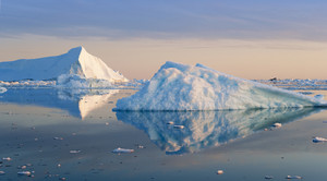 Iceberg and ice floe in the water at dusk