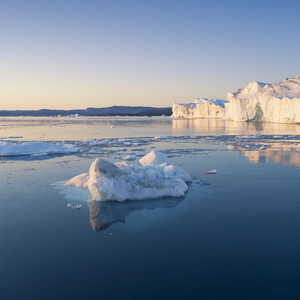 Iceberg and ice floe reflected in the water at dusk