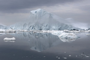 Iceberg and ice floe reflected under a grey, foggy sky