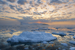 Iceberg and ice floe under a cloudy sky at sunset