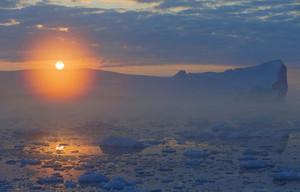 Iceberg and ice floes at sunset