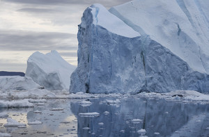 Iceberg and ice floes reflected in icy waters under a grey sky