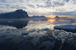 Iceberg and ice floes under a golden sunset