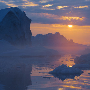 Iceberg and ice floes under a misty sunset