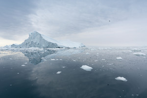 Iceberg and ice floes under a stormy sky