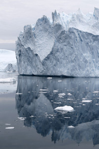 Iceberg in icy waters reflected under a grey sky