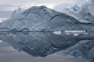 Iceberg reflected in calm waters under a grey sky