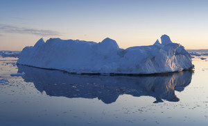 Iceberg reflected in clear water at dusk