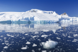 Iceberg reflected in icy waters under a blue sky