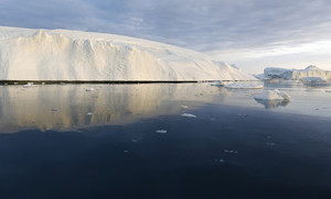 Iceberg reflected in icy waters under a cloudy sky