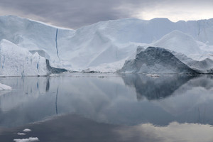 Iceberg reflected in still waters against a cloudy sky