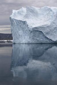 Iceberg reflected under a grey sky along the coast