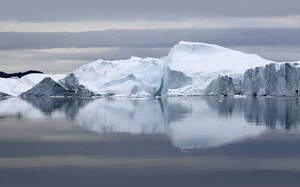 Iceberg reflected under a grey sky