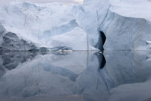 Iceberg with a crevasse reflected under a grey sky