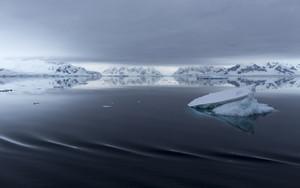 Icebergs in dark waters under a stormy sky