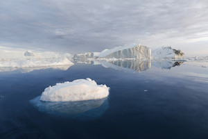 Icebergs reflected in calm waters under a grey sky