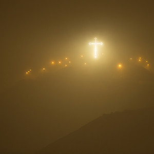 Illuminated cross on a hill at night