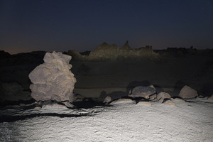 Illuminated rocks on a barren landscape at night