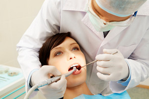 Image of a dentist curing a girl's teeth