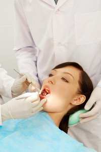 Image of a girl examined by two dentists