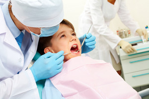 Image of dental examining being given to little boy by dentist