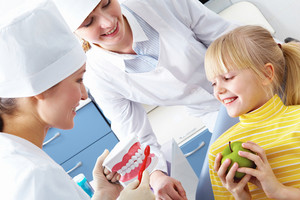 Image of dentist showing care dental hygiene to little girl with assistant near by