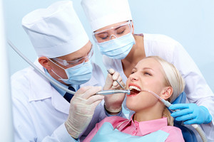 Image of dentist treating woman's teeth and assistant near by