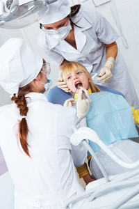 Image of doctor checkup little girl's teeth with assistant near by