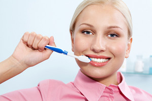 Image of happy female holding toothbrush in hand before cleaning teeth