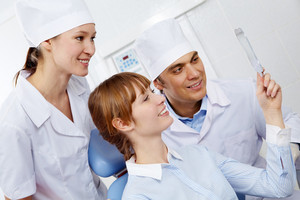 Image of patient looking in mirror with doctor and assistant near by